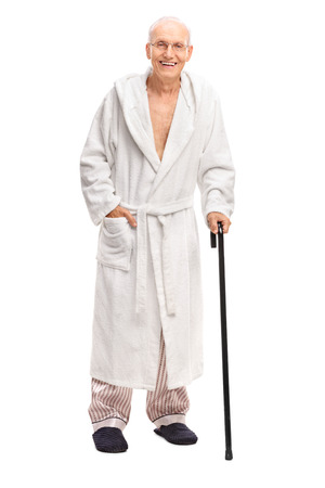 old people walking: Full length portrait of a senior man in a bathrobe holding a cane and looking at the camera isolated on white background