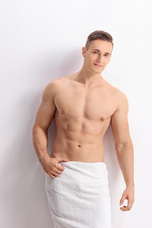toallas: Tiro vertical de un hombre sin camisa guapo posando sobre una pared blanca con una toalla de baño