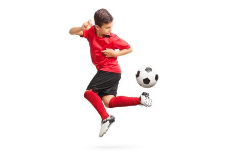 Foto de estudio de un jugador de fútbol junior realizando un truco con un balón de fútbol aislado sobre fondo blanco. Foto de archivo