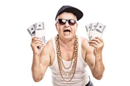 Delighted senior in hip hop outfit holding a few stacks of money and looking at the camera isolated on white background