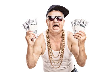 Opgetogen senior in hip hop outfit met een paar stapels geld en kijken naar de camera op een witte achtergrond