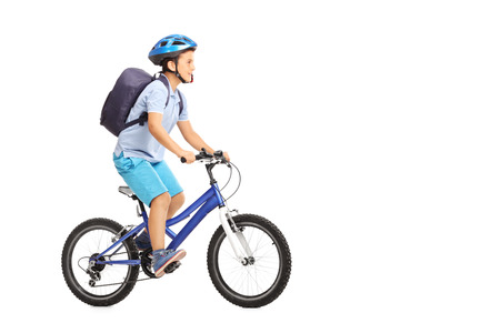 Studio shot of a schoolboy with a helmet and a blue backpack riding a bike isolated on white background Foto de archivo