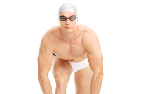 trunk: Studio shot of a young male swimmer in white swim trunks getting ready to jump isolated on white background