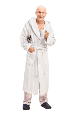 robes: Full length portrait of a senior man in a white bathrobe holding a newspaper and a coffee mug isolated on white background Stock Photo