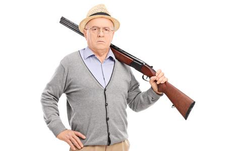 cazador: Caballero mayor que presenta con un rifle aislado en fondo blanco Foto de archivo