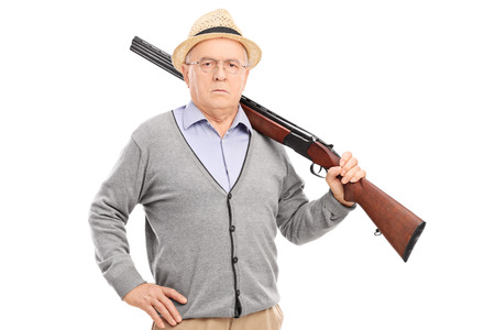 Senior gentleman posing with a rifle isolated on white background