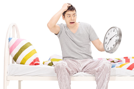 overslept: Shocked young man sitting on a bed in his pajamas and looking at the time isolated on white Stock Photo