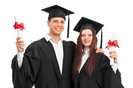 toga y birrete: Pareja joven posando con sus diplomas aislado en fondo blanco