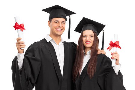 cap and gown: Young couple posing with their diplomas isolated on white background