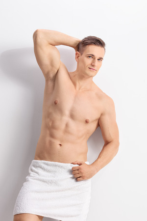 Vertical shot of a handsome young man posing with a white bath towel around his waist and looking at the camera Stock Photo