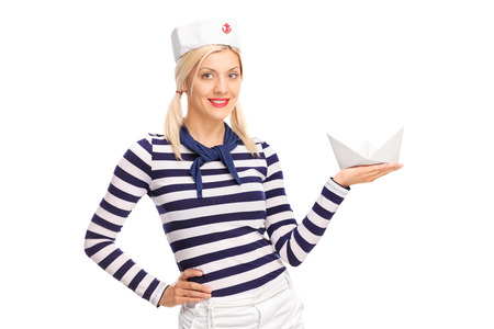 small paper: Young female sailor holding a small paper boat and looking at the camera isolated on white background