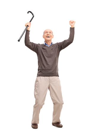 Full length portrait of an overjoyed senior holding a black cane an looking up isolated on white background