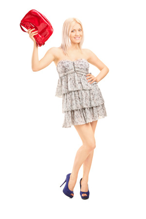 red purse: Full length portrait of a fashionable blond girl holding a red purse and looking at the camera isolated on white background