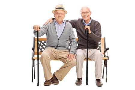 hombre sentado: Estudio tirado de un dos amigos maduros posando juntos sentado en un banco de madera aislada sobre fondo blanco