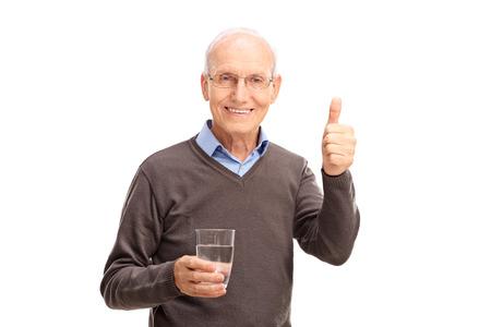 Studio shot van een senior man die een glas water en het geven van een duim omhoog op een witte achtergrond