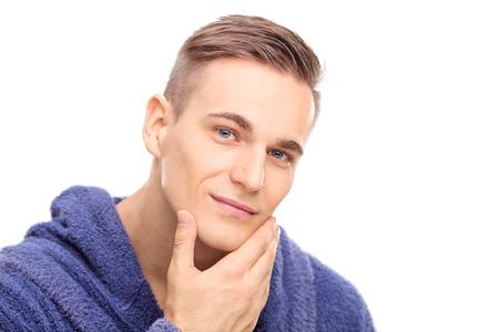 Studio shot van een jonge man het controleren van de huid op zijn gezicht op een witte achtergrond