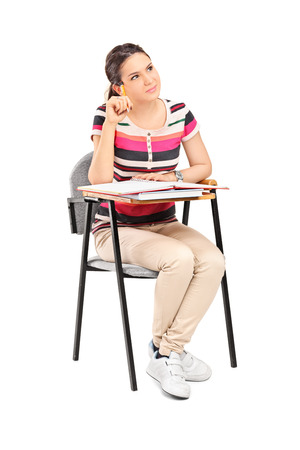 Vertical shot of a pensive female student sitting on a school desk and thinking isolated on white background photo