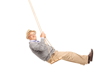 Carefree senior man swinging on a wooden swing and looking at the camera isolated on white background
