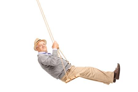 Hombre mayor Despreocupado balanceándose en un columpio de madera y mirando a la cámara aislada en el fondo blanco Foto de archivo - 42870425