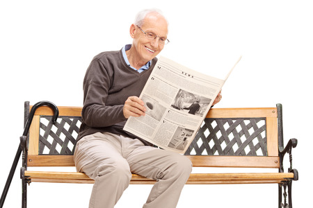 old man sitting: Senior man reading a newspaper seated on a wooden bench isolated on white background
