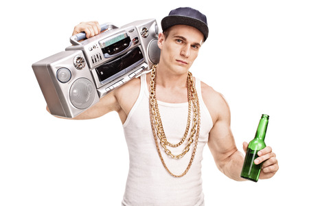 baile hip hop: Rapero masculino joven que lleva un ghetto blaster por encima del hombro y sosteniendo una botella de cerveza aislado sobre fondo blanco