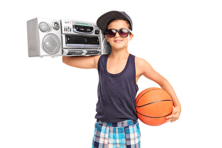 Studio shot of a little boy holding a basketball and a ghetto blaster isolated on white background Stock Photo