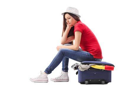 over packed: Triste giovane ragazza seduta su una valigetta piena di abiti e di pensiero isolato su sfondo bianco