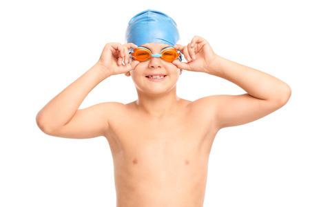 niño sin camisa: Niño pequeño con gafas de natación de color naranja y gorra azul baño mirando a la cámara aislada en el fondo blanco Foto de archivo