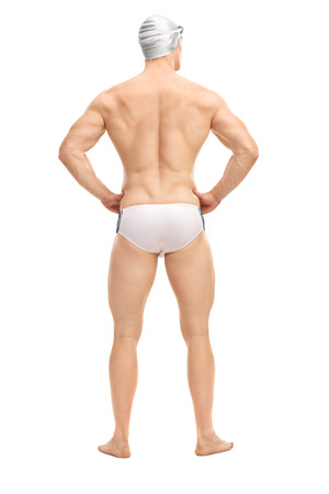 trunk: Full length rear view shot of a handsome male swimmer in white swim trunks and a gray swim cap isolated on white background