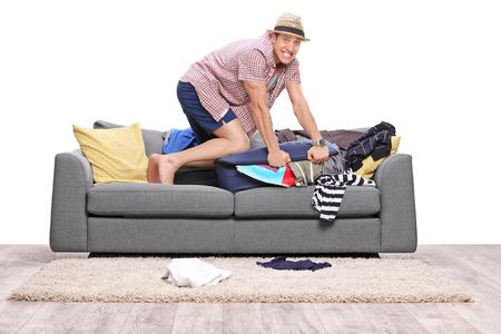 valise voyage: Jeune homme d'emballage beaucoup de vêtements dans une valise et en regardant la caméra isolée sur fond blanc Banque d'images