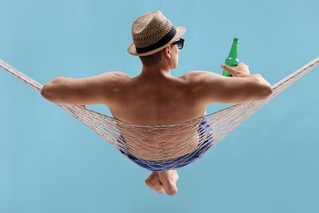 hamaca: Posterior disparo opinión del estudio de un hombre joven despreocupado tumbado en una hamaca y con una botella de cerveza en el fondo azul