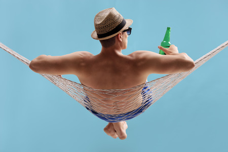 Rear view studio shot of a carefree young man lying in a hammock and holding a bottle of beer on blue background Zdjęcie Seryjne