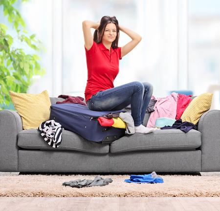 habitacion desordenada: Mujer joven trastornado que se sienta en su maleta en casa y tratar de encajar toda su ropa en ella disparó con inclinación y desplazamiento de la lente Foto de archivo