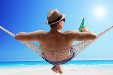 Relaxed jonge kerel liggend in een hangmat en het drinken van bier op een zonnig strand door de oceaan