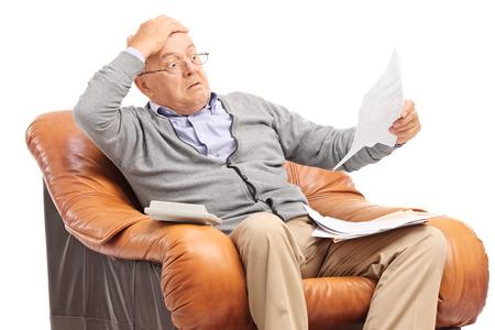 Caballero mayor Shocked mirando sus facturas en incredulidad sentados en un sillón aislado en fondo blanco