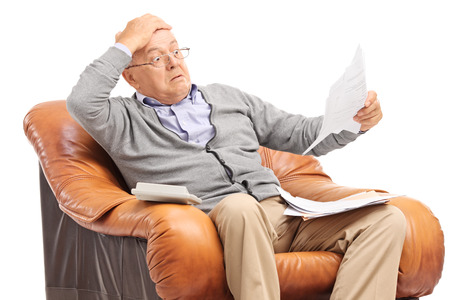 Shocked senior gentleman looking at his bills in disbelief seated in an armchair isolated on white background Stockfoto