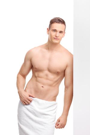 Tiro vertical de un individuo joven hermoso vestido sólo con una toalla de baño blanca alrededor de su cintura apoyado contra una pared y mirando a la cámara aislada en el fondo blanco Foto de archivo