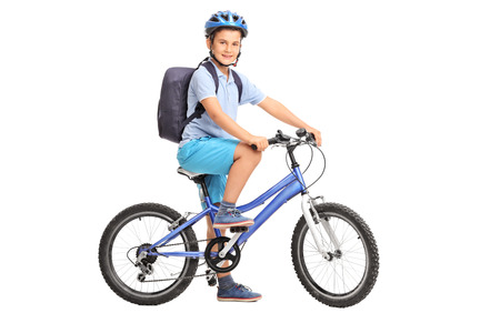 riding: Studio shot of a schoolboy riding a bicycle and looking at the camera isolated on white background