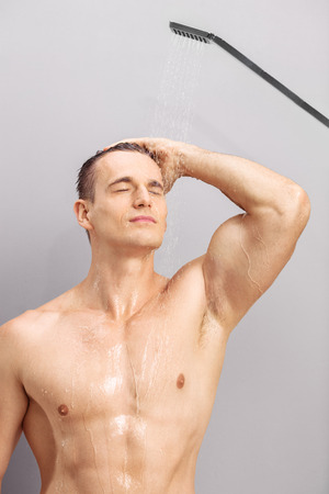 scrubbing: Vertical shot of a handsome young guy taking a shower and scrubbing his hair