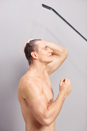 taking shower: Vertical profile shot of a young man taking a shower on gray background Stock Photo
