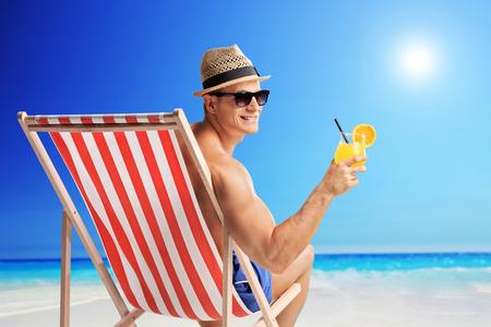 hombre sentado: Hombre joven alegre que sostiene un c�ctel de naranja sentado en una tumbona en una playa junto al mar