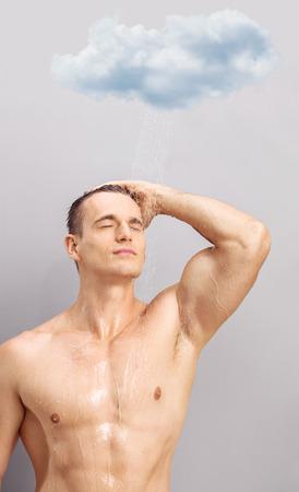 tomando refresco: Tiro vertical de un apuesto joven de tomar una ducha debajo de una pequeña nube de lluvia sobre fondo gris
