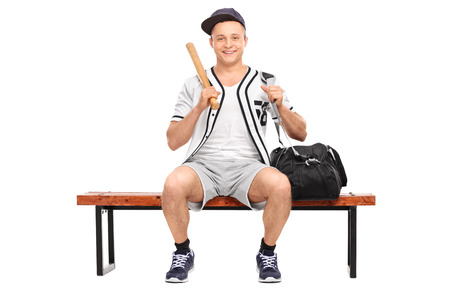 player bench: Young baseball player holding a baseball bat and sitting on a wooden bench isolated on white background