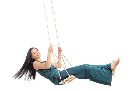 columpio: Mujer de moda balanceándose en un columpio de madera y mirando a la cámara aislada en el fondo blanco
