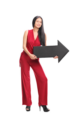 flechas: Full length portrait of a young fashionable woman holding a big black arrow pointing right isolated on white background Foto de archivo