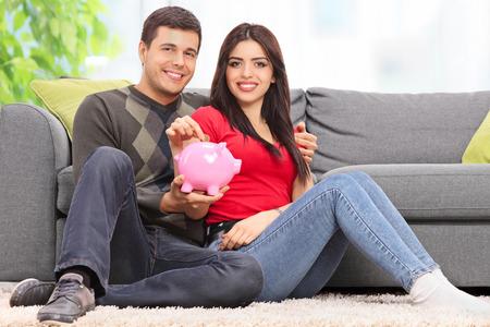 parejas jovenes: Pareja joven posando con una hucha sentado en el suelo de un sofá de color gris en el hogar