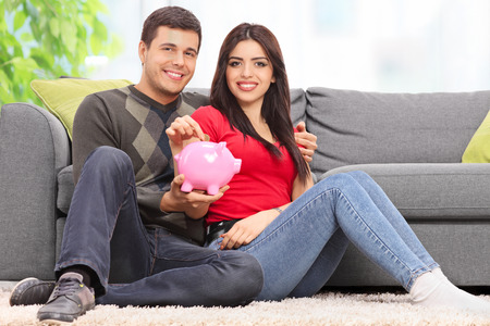 Young couple posing with a piggybank seated on the floor by a gray sofa at home