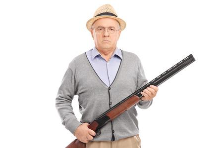 hombre con sombrero: Caballero mayor serio la celebración de una escopeta y mirando a la cámara aislada en el fondo blanco Foto de archivo