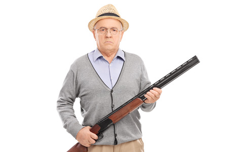 gun man: Serious senior gentleman holding a shotgun and looking at the camera isolated on white background