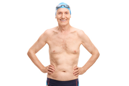 senior men: Shirtless senior in black swim trunks and blue swimming cap looking at the camera and smiling isolated on white background